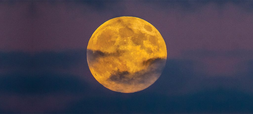 Super Full Moon captured in a golden color between a cloudy sky